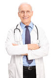 Mature doctor posing in white coat Stock Images