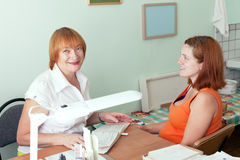Mature doctor and pregnant woman. Mature doctor and pregnant women in clinic royalty free stock photos