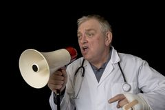 Mature doctor protesting and shouting into a megaphone. On a black background Stock Image