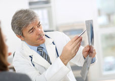 Mature doctor showing x-ray results Stock Photography