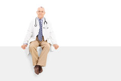 Mature doctor sitting on a blank panel Royalty Free Stock Photo