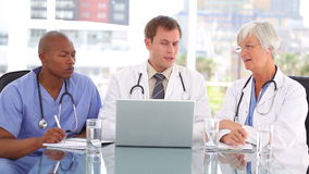 Mature doctor sitting with her team while looking at a laptop Stock Photo