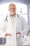 Mature doctor smiling in lab coat. In his room Stock Images