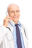 Mature doctor speaking on a telephone and smiling. Vertical shot of a mature doctor speaking on a telephone and smiling isolated on white background Stock Images