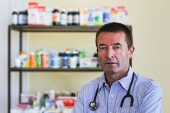 Mature Doctor Standing In Front Of Medicine Stock Image