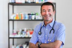 Mature Doctor Standing In Front Of Medicine Royalty Free Stock Image