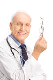 Mature doctor taking off his glasses Royalty Free Stock Photos
