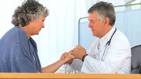 Mature doctor taking the pulse of his patient Stock Image
