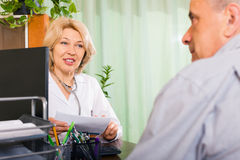 Mature doctor talking with elderly male patient Stock Photos