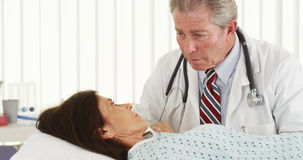 Mature doctor talking to patient in hospital bed. Mature doctor talking with female patient Stock Image