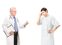 Mature doctor talking to a worried male patient Stock Images