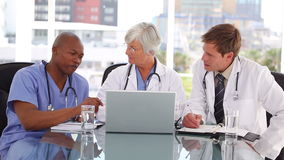 Mature doctor talking with two colleagues. In a bright room stock video footage