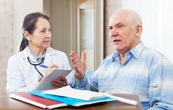 Mature doctor talks with  senior man Stock Photo