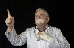 Mature doctor with tape across his mouth and pointing towards the sky stock photos