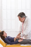 Mature doctor touches belly of teenager patient in Royalty Free Stock Photos