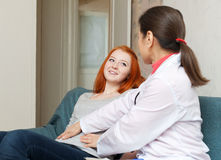 Mature doctor touching  belly of teenager Royalty Free Stock Photos