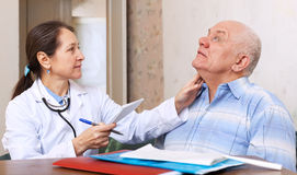 Mature doctor touching  neck of   man Stock Images