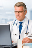 Mature doctor at work Royalty Free Stock Image