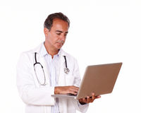 Mature doctor working on his laptop Royalty Free Stock Photography