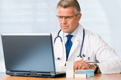 Mature doctor working on laptop. And medication's cases to make prescriptions in his clinic office Stock Photo