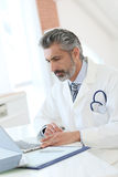 Mature doctor working on laptop Royalty Free Stock Image