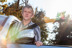 Mature driver standing near car with opened door and sunlight on background Stock Images