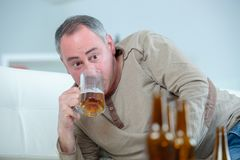Mature drunk man drinks beer on sofa Stock Photo