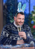 Mature dude wearing bunny ears on New Year Eve. Middle-aged man in blue bunny ears sits at the desk with glass of white dry wine. Bearded dude in Scandinavian Royalty Free Stock Photography