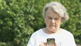 Mature elderly woman holds a smart phone outdoors stock video footage