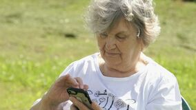 Mature elderly woman holds a mobile phone outdoors stock video