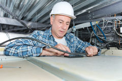 Mature electrician fixing wiring in ceiling Stock Photo