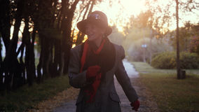 Mature elegant happy woman in age wears in coat and hat dancing in the park outdoor Stock Photos