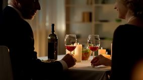 Mature elegant male and female holding wine glasses looking each other with love stock photography