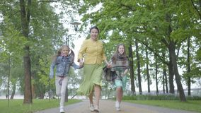 Mature elegant woman running in the park with her two granddaughters holding hands. Grandmother spending time with stock video footage
