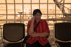Mature elser asian woman is calling on a cell phone . Royalty Free Stock Image
