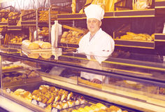 Mature employee with tasty confectionery products. On counter of bakery Royalty Free Stock Photo