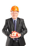 Mature engineer holding a small model house Stock Photos