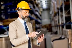 Mature engineer in the warehouse with digital tablet Stock Image
