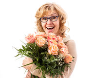 Mature, enthusiastic woman with bouquet of roses Royalty Free Stock Photos
