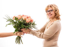 Mature, enthusiastic woman with bouquet of roses Stock Photography