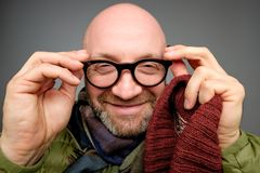 Mature european man wearing a pair of geek glasses squinting cause he can not see. Close up portrait of male with bad eyesight royalty free stock photography
