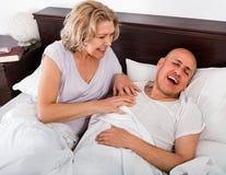 Mature evil girl looking at snoring boyfriend. Sleeping tight Royalty Free Stock Photos