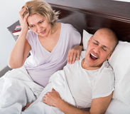 Mature exhausted woman disturbed with partner snores Stock Photography