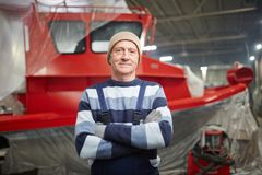 Engineer and boat. Mature experienced shipbuilding engineer standing on background of new red boat in factory Royalty Free Stock Photos