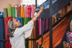 Mature woman checking inventory in her fabric shop. Mature fabric shop owner working in her store surrounded by colorful cloths and textiles taking inventory Royalty Free Stock Images