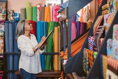 Mature woman doing inventory in her fabric shop. Mature fabric store owner standing in her shop surrounded by colorful cloths and textiles taking inventory with Royalty Free Stock Photo
