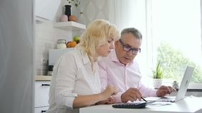 Mature family couple accounting budget in cozy kitchen.