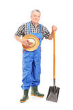 Mature farmer holding a shovel. Full length portrait of a mature farmer holding a shovel  on white background Royalty Free Stock Photos