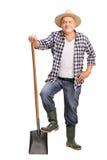 Mature farmer posing with a shovel stock image