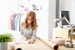 Mature fashion designer working in her studio Stock Image